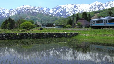 Train passes by Hakuba Village,reflected with snowy mountain
