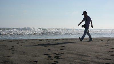 waves at the beach,man walks through frame