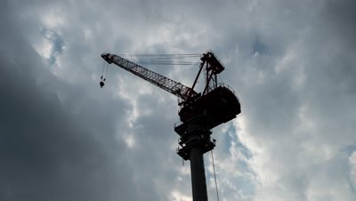 Time lapse view of clouds moving behind silhouetted construction crane