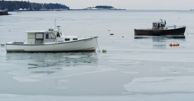 Fishing vessels moored in ice covered harbor