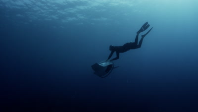 A free diver glides underwater with a non motorized / gravity contraption called a Dive Glide.