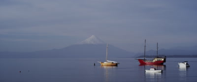 Boats anchored on Lake Llanquihue with a snow caped Osorno Volcano