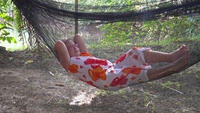 Little girl swinging in a hammock in the jungle, 4k