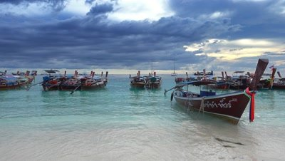 Long tail boats at the white sand beach on the storm clouds background, Koh Lipe, Thailand, 4k