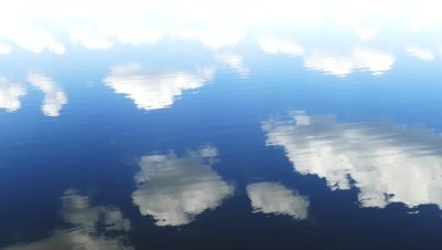 circles flow along surface of water, in water reflects sky with clouds, 4k