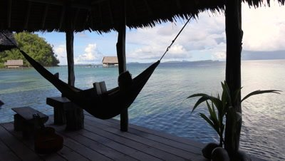 Person reading book in hammock on terrace of bungalow at tropical island resort