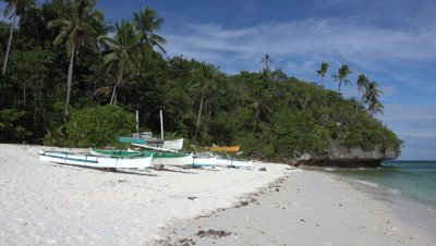 Pan over beach with banka on Bohol Island