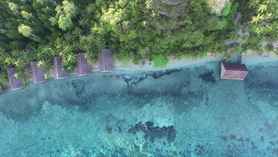 Descending down on beach with water bungalows on Pulau Pef in Raja Ampat