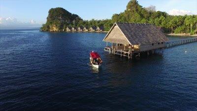 Dive boat leaving pier on Pulau Pef in Raja Ampat