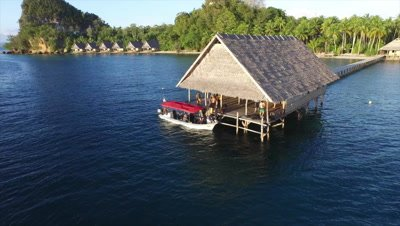 Divers getting into dive boat from pier at Pulau Pef in Raja Ampat