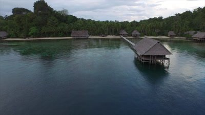 Flying along long wooden pier towards the remote island of Pulau Pef in Raja Ampat