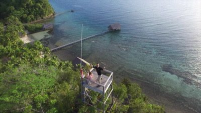 Hikers celebrating their ascent to a hill on Pulau Pef in Raja Ampat