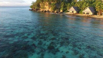 Snorkeler enjoying pristine house reef at remote resort in Raja Ampat at sunset