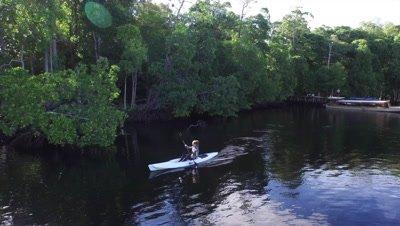 Woman cayaking along mangroves in Raja Ampat
