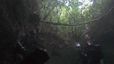 Two divers chatting on surface, filmed from under water