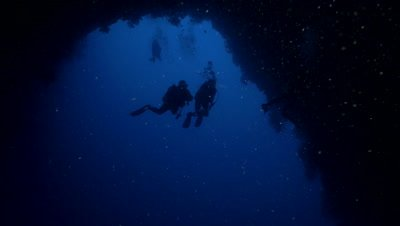 group of scuba divers enter huge under water cave,arch,Palau