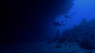group of scuba divers enter huge under water cave,Palau