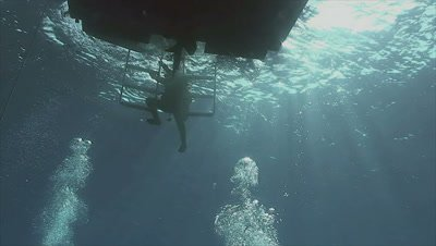 underwater shot of scuba diver leaving water on boat,uses ladder