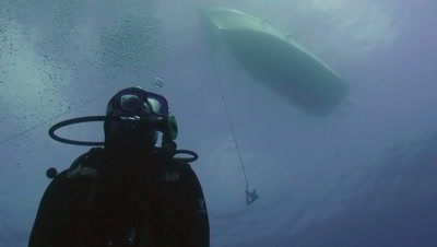 underwater shot of scubadiver,low angle,boat plus anchor in background
