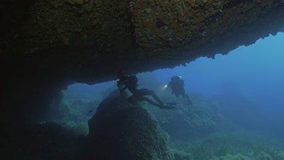 4K under water shot of scuba divers entering underwater cave