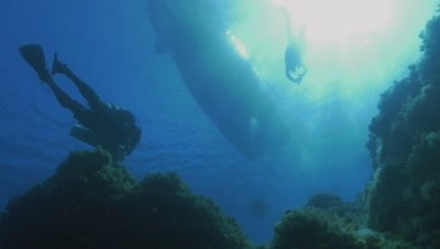 underwater shot of scuba divers swimming towards boat,low angle shot