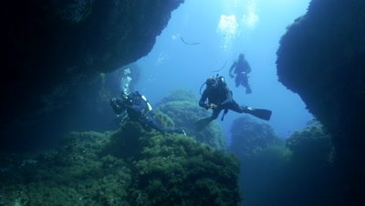 4K under water shot of group of scubadivers entering cave