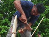 Smiling Indonesian Boat Builder Chiselling Timber At Bunaken Village