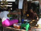 Burmese Woman Pays For Goods At A Market In Kaw Thaung, Myanmar