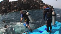 Scuba Divers Jump Into The Water From A Dive Boat