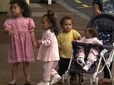 Children Holding Hands On Busy Street, Baby In Pram With Mother Walk To Kerb To Wait For Crossing