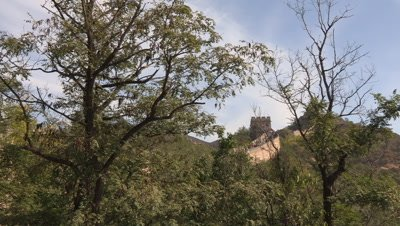 Tourists walking on the Great Wall of China, partially obscured by the surrounding forest