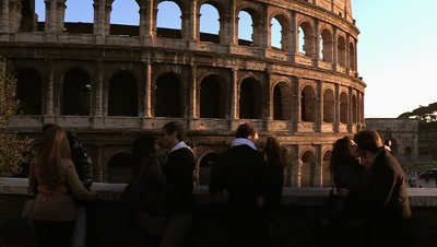 Couples kissing in front of the Colosseum in Rome