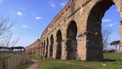People bicycling past the Aqua Claudia ruins, an ancient Roman aqueduct at Roma Vecchia