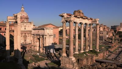 Tourists visiting the ruins of the Temple of Saturn and the Temple of Vespasian and Titus in the Roman Forum