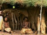 Women And Children Sitting Outside Large Flax Hut