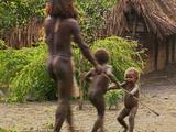 Man & Two Children Walk Backwards Into Shot, Holding Sticks Together