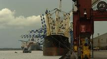 Ship Docked At Wharf, Cranes, Small Boat Motors In, Other Ships In B/G