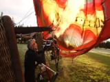 Man In Sunglasses Fires Up Burners Of More Fm Hot Air Balloon, Interior View Of Balloon As Basket Lies On Ground