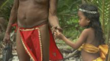 Historical Reenactment Of Kalinago People Arriving On Beach In The Caribbean, Man shows girl a crab