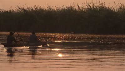 Two Fisherman in mokoro at sunrise on river