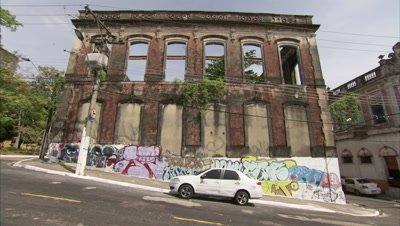Man Walks on Street past Derelict Building