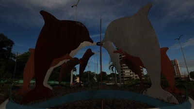 Time Lapse Cars Behind dolphin sculpture on roundabout