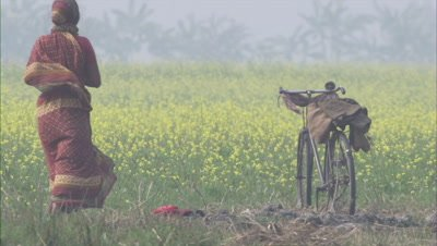 Bicycle Parked Near Crop Field,Woman Villager Passes By