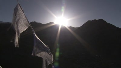 Rising or Setting Sun Behind Mountain,Prayer Flags Foreground