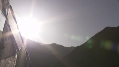 Prayer Flags with Mountains and Sun Behind