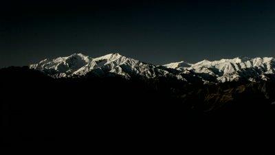 Time Lapse,Sunrise Illuminates snow-capped mountain range behind eroded hills