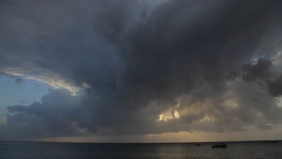 Time lapse of clouds and sunset with boats moving on ocean's surface in the foreground