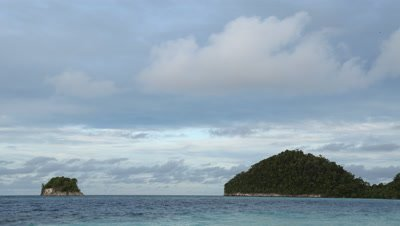 Time lapse of cloudy skies over islands with ocean in the foreground.