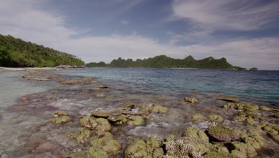 Waves lapping over coral seascape with forest covered limestone islands in distance