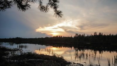 Timelapse of sunset with clouds moving over forest and a water body in foreground